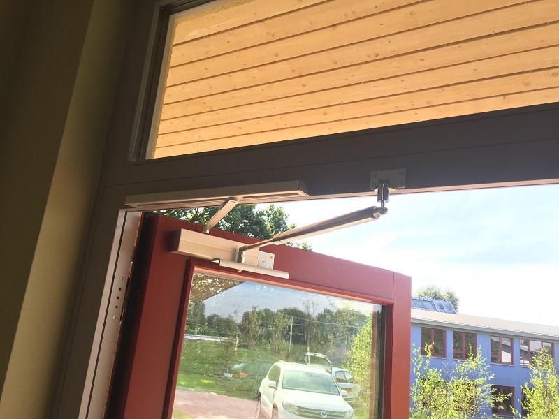 Door with overhead door closer and back check